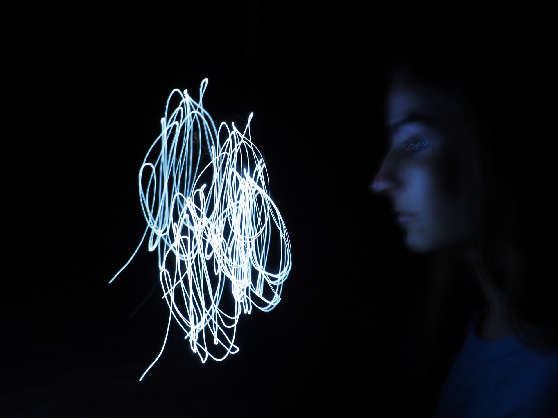 A Self portrait of Erika Degoute Photographer in Sydney showing her looking intensely at a knot of light in a dark room in front of her