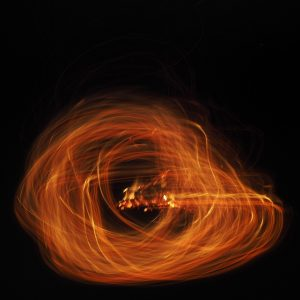 An abstract picture of loose fire brushes in a circular motion on a black background using light painting technique