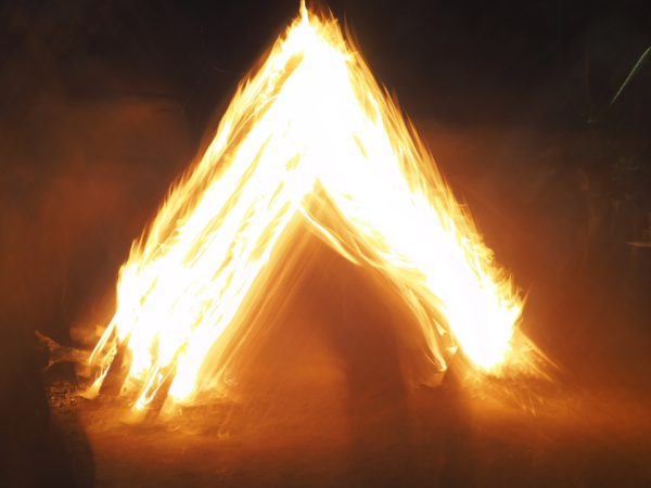 An abstract picture of a triangle of fire on a black background using light painting technique