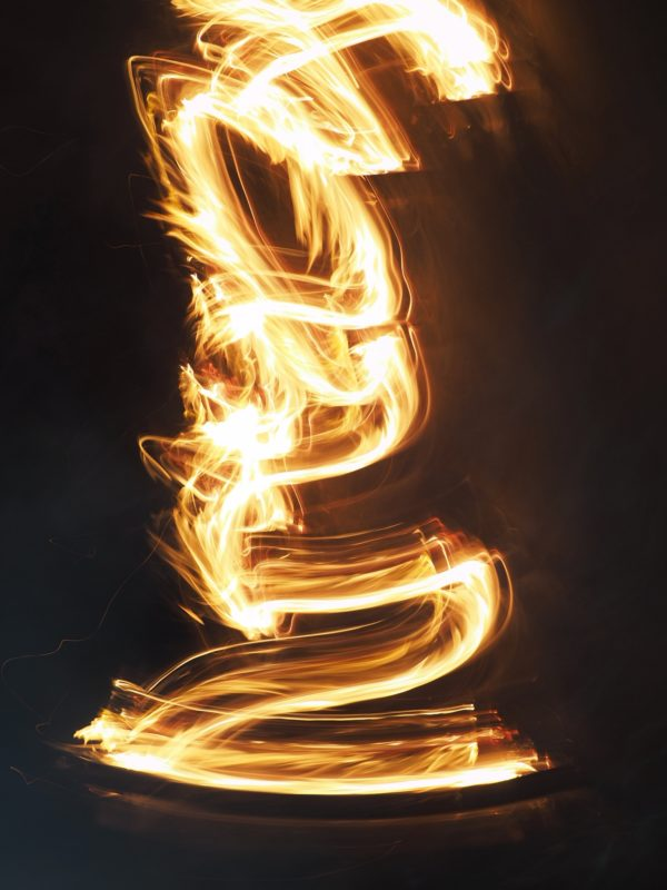 An abstract picture of fire filaments reaching for the sky on a black background using light painting technique