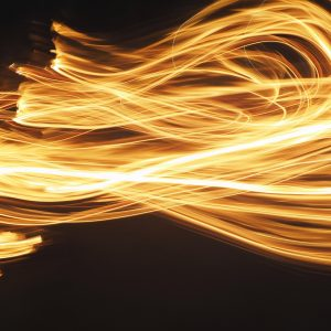 An abstract picture of loose fire brushes in a figure 8 pattern on a black background using light painting technique