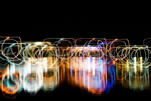 An abstract picture showing spills with their top flattened using light painting technique with vivid mixed rainbow colors on a black background