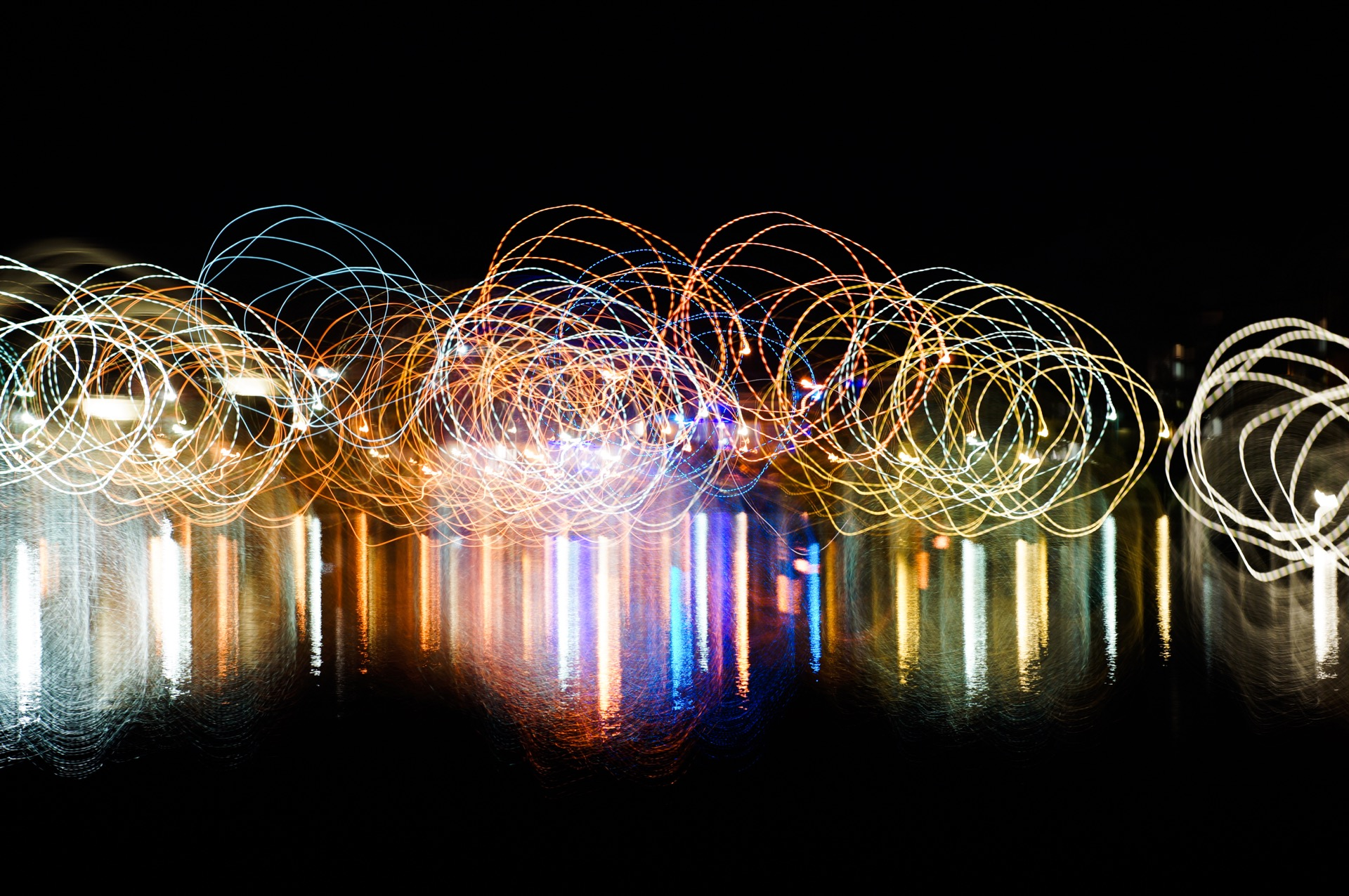 An abstract picture showing small spirals using light painting technique with vivid mixed rainbow colors on a black background