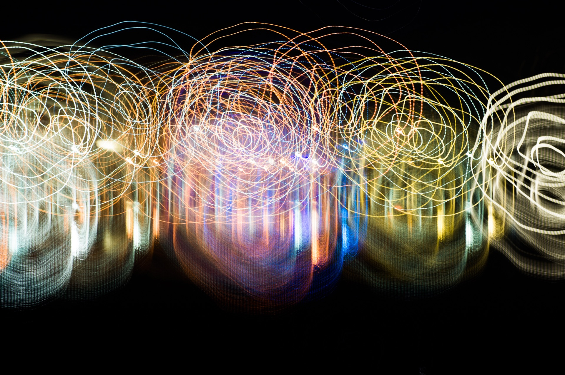 An abstract picture showing large spirals using light painting technique with vivid mixed rainbow colors on a black background