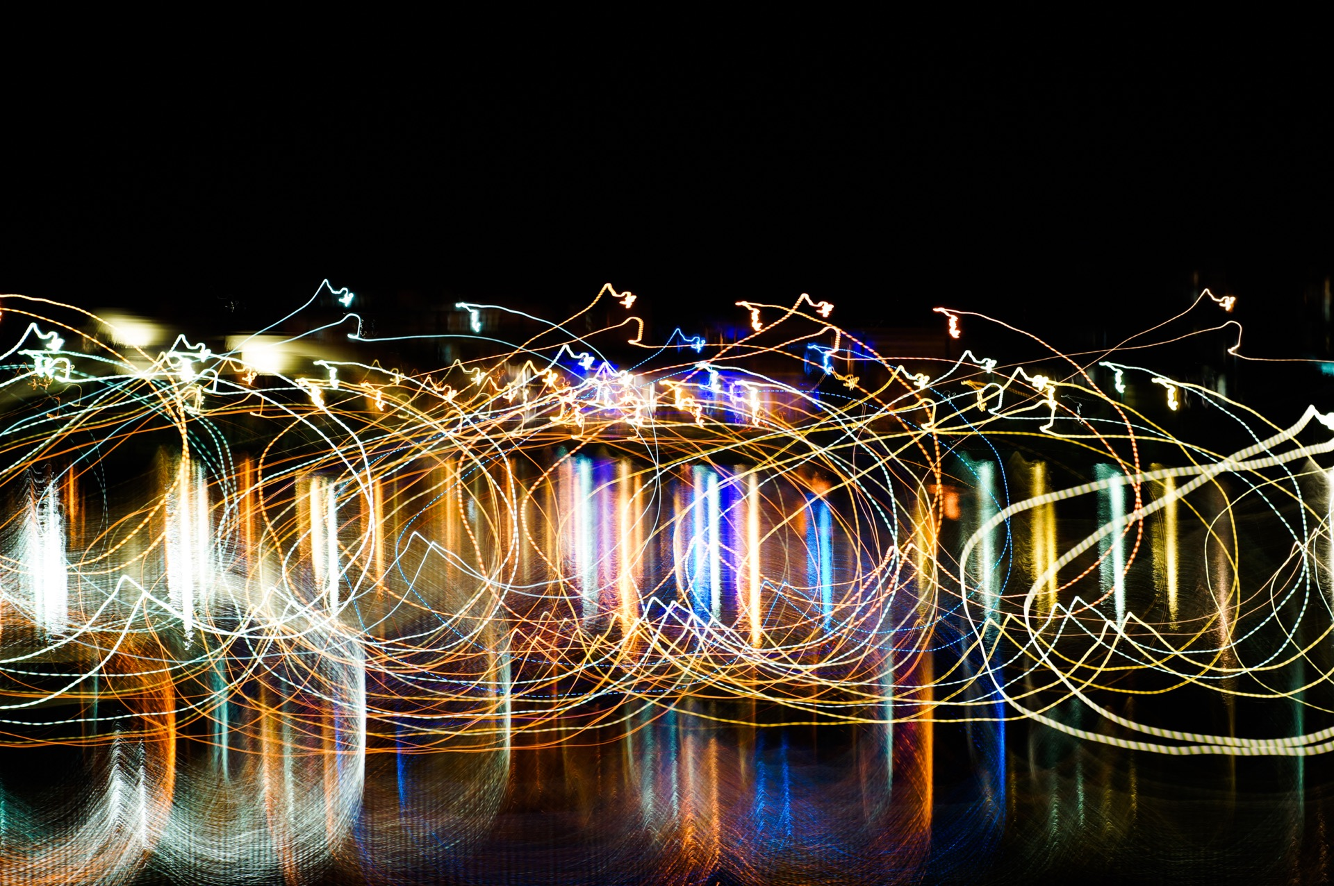 An abstract picture showing purse shapes using light painting technique with vivid mixed rainbow colors on a black background