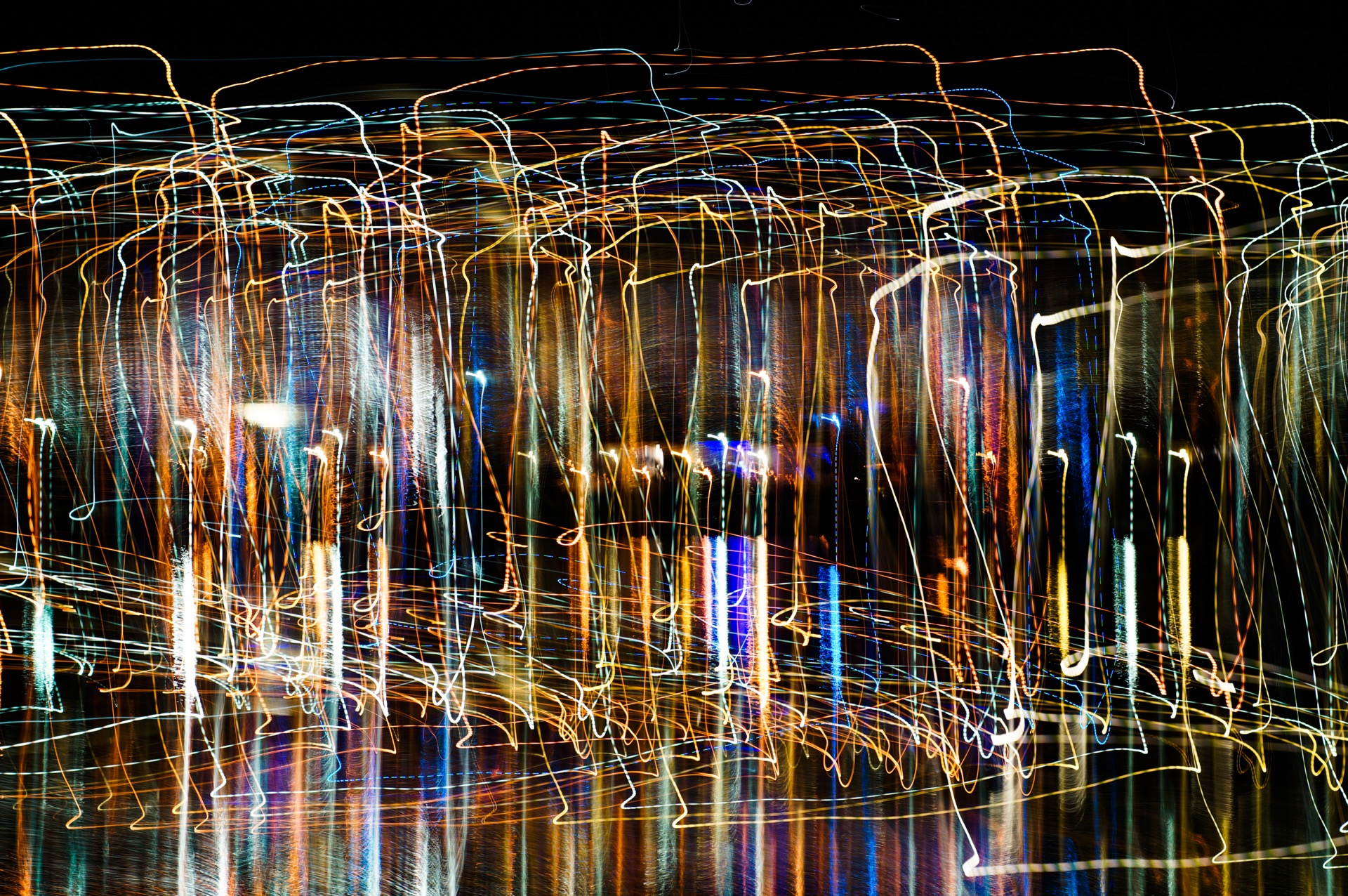 An abstract picture showing large vertical rectangles using light painting technique with vivid mixed rainbow colors on a black background