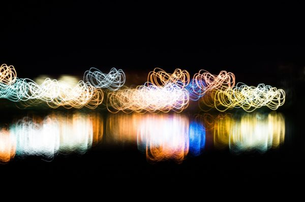 An abstract picture showing eternity loops symbols using light painting technique with vivid mixed rainbow colors on a black background
