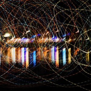 An abstract picture showing extra large spirals using light painting technique with vivid mixed rainbow colors on a black background