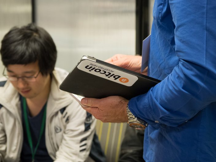 A man holding a tablet with a Bitcoin sticker on it