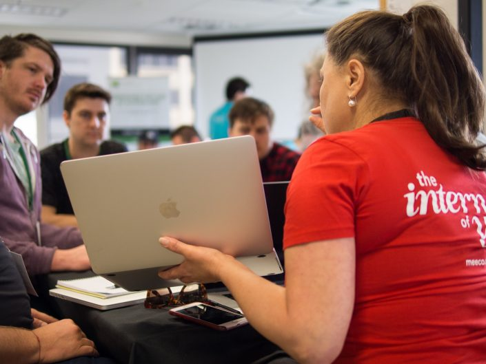 A woman hackathon mentor speaking with her laptop open to a small team group of people