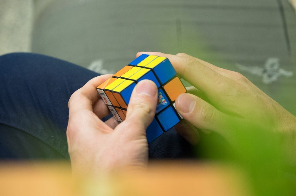 A man's hands playing with Rubik's Cube
