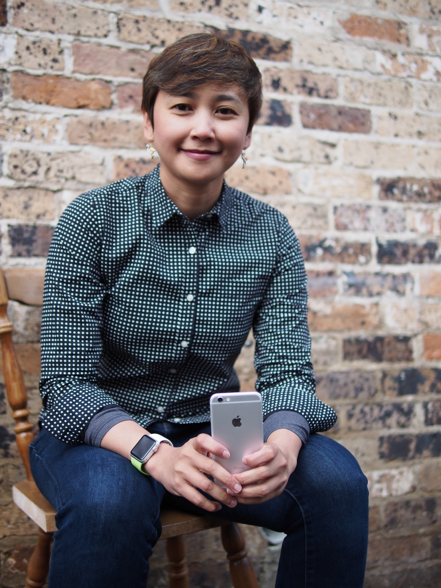A picture of someone holding an iPhone 6 and sitting in front of a sand coloured brick wall